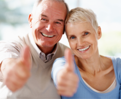an old couple showing their thumbs up